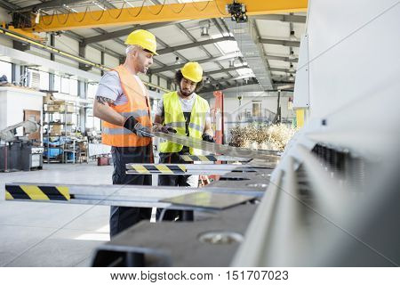 Male manual workers examining sheet metal at industry poster