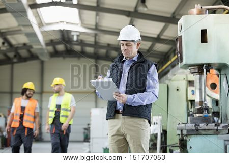 Mature male inspector writing on clipboard while workers in background at industry