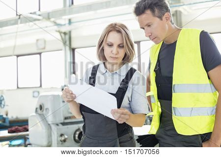 Male and female manual workers examining paper in industry