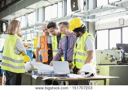 Supervisor and manual workers discussing over blueprints in industry