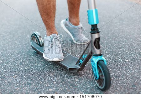 Close-up of a scooter on the asphalt. Kick scooter. Man riding scooter