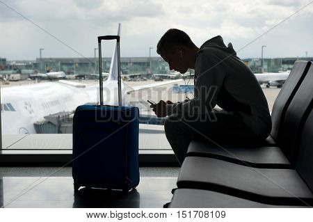 A teenager is waiting on an airport and playing with his smartphone