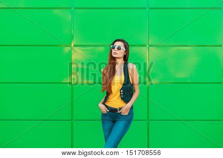 Beautiful Woman In A Yellow T-shirt And Denim Jacket Standing Near A Green Metal Wall.