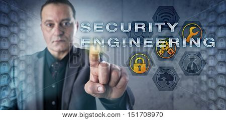 Experienced engineer with intent facial expression is touching SECURITY ENGINEERING on a screen. Information technology concept and corporate security metaphor for robust system design solutions.