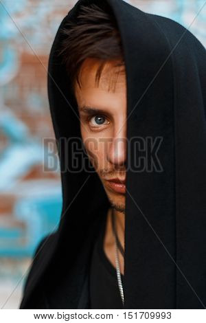 Portrait Of A Handsome Man In A Black Hood. Hidden Face.