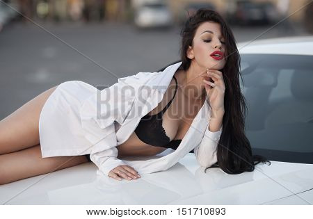 Young sexy brunette woman in black lingerie and white shirt on sport car hood.