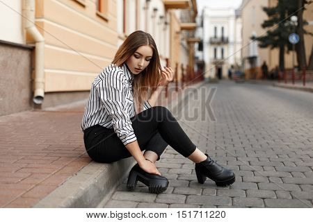 Beautiful Stylish Young Woman In Striped Blouse Sitting On The Curb.