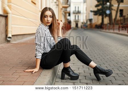 Young Beautiful Woman In Fashionable Clothes Sitting On The Curb