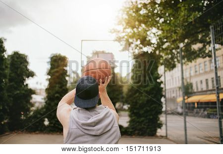 Rear view shot of a young guy playing basketball on outdoor court. Streetball player shoots basket.
