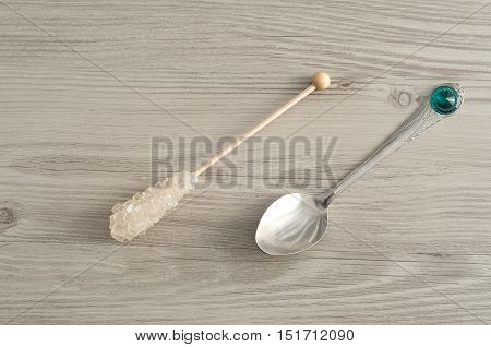 A sugar stick and a teaspoon isolated against a wooden background