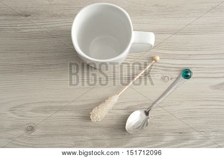 A white mug with a sugar stick and a teaspoon isolated against a wooden background