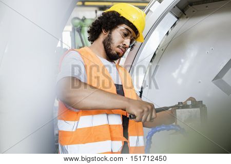 Young manual worker tightening bolts on machinery in factory