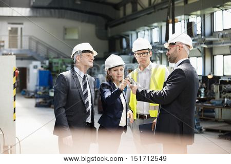 Team of business people examining machine part in metal industry