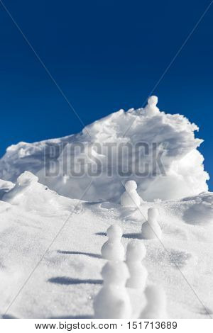 Snowmen Climbing Up To A Icy Mountaintop