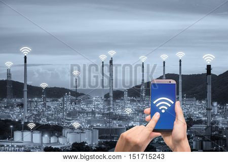 Hand holding smartphone control wireless communication network smart factory and Internet of Things. Smart factory concept.
