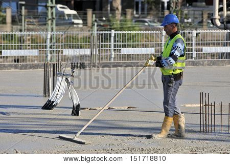 DUSSELDORF GERMANY - OCTOBER 5: Construction worker during processing concrete on the building's construction in Duesseldorf Germany on October 5 2016