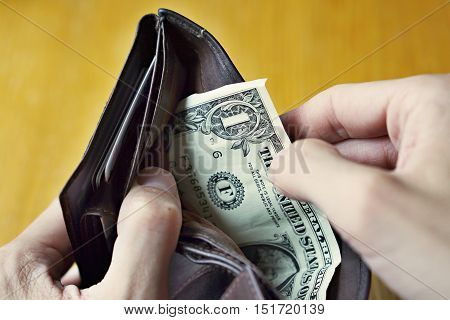 Male hands opening an almost empty leather wallet with only one American dollar (One USD, US dollar) as a symbol of modern poor person from a developed country, poverty and economic crisis