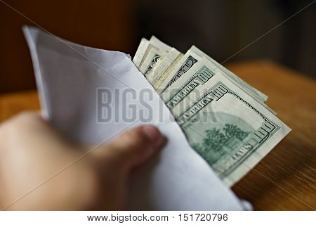 Male hand holding and passing a white envelope full of American Dollars (USD, US Dollars) as a symbol of illegal cash transfer, money laundering or bribery