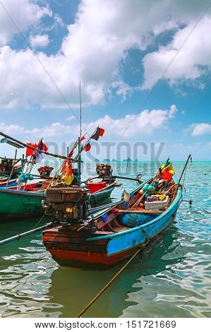 Colored fishing boats in the sea on the turquoise waves. And colorful tackle and networks are for wooden boats.