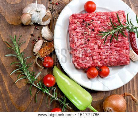 Raw fresh ground beef meat - minced meat on plate and spice (seasoning) with vegetable