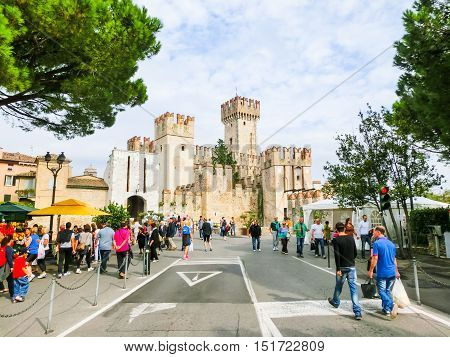 Sirmione, Italy - September 20, 2014: The people going to the Scaliger Castle. The famous castle of Sirmione and its small port are an uncommon example of a fortress used as a port. The building of this complex started in 1277 by Mastino della Scala.