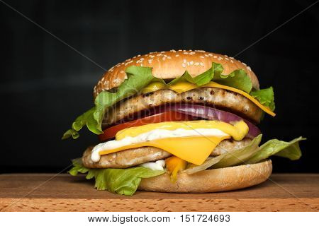 A delicious huge burger with two cutlets on a wooden board on a dark background.  Photo causing appetite. The concept of fast food, delicious food but unwholesome.