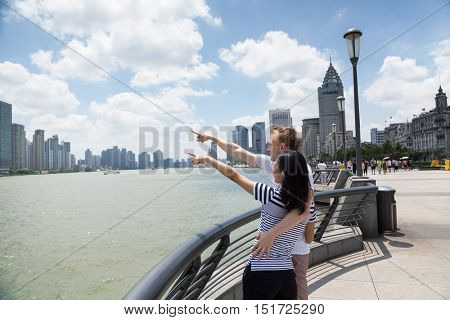 Couple pointing at cityscape while standing on promenade in Shanghai