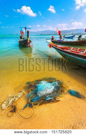 Colored fishing boats in the sea in the turquoise waters. And colourful tackle and nets on the sand