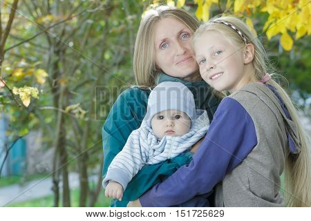 Fall outdoor family portrait of cheerful mother with two siblings at bright yellow autumn shrubbery leaves background