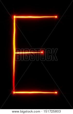red light painting letter E on black background