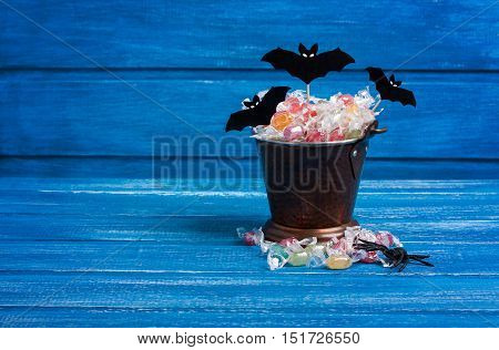 Halloween candy bucket paper bats and rubber spider on blue wooden backround horizontal orientation