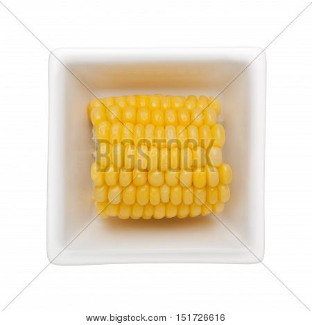 Corn cob in a square bowl isolated on white background