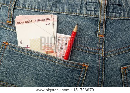 Malaysian money and lottery betting slip in back pocket