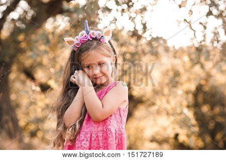 Smiling baby girl 4-5 year old wearing unicorn hairband and pink dress outdoors. Childhood.