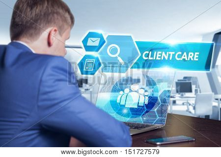 Business technology internet and networking concept. Young businessman working on his laptop in the office select the icon client care on the virtual display.