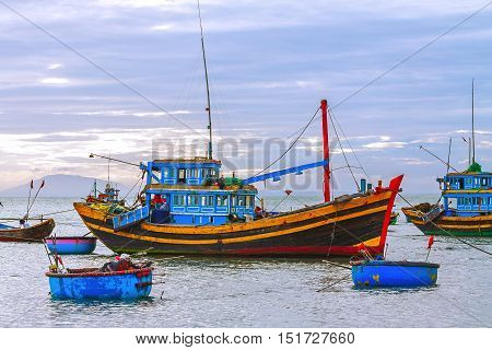 Colored fishing boats in the sea on a background of mountains and sky at sunset.
