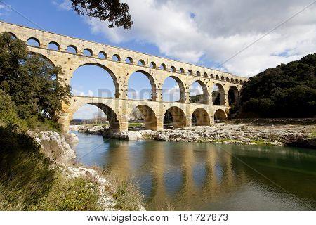 Pont du Gard. Blue sky. Reflection in water.