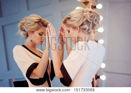 Attractive woman in evening dress, the reflection in the mirror in the background