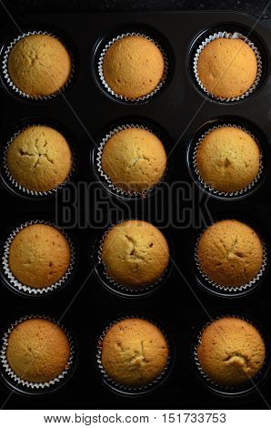 Overhead of a dozen golden cup cakes straight from the oven baked in paper cases and still inside black bun tin.