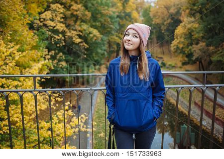 Stylish Sporty Brunette Woman Hands In Pockets In Trendy Urban Outwear Posing At Bridge Forest City