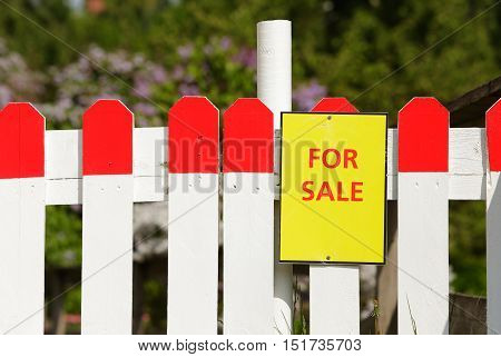Advertising a for sale sign on a wodden fence.