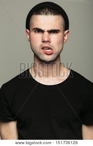 Studio portrait of provocative angry young man looking at camera on gray background.