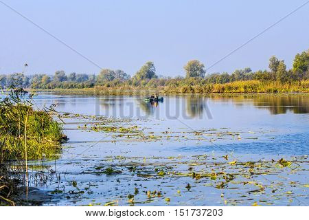 The river Chaus Kolyvan district Novosibirsk oblast Siberia Russia - September 17 2016: fishermen in an inflatable rowing boat with a spinning rod looking for a predatory fish on the river