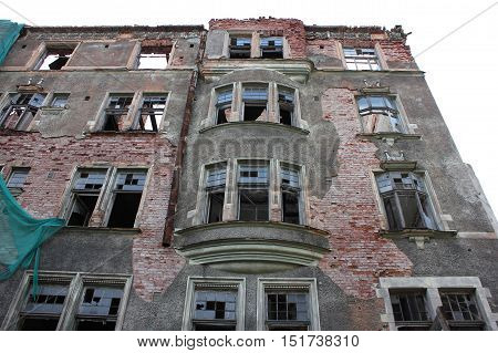 Abandoned destroyed crumbling old residential apartment housing building facade. Damaged house in need of renovation. Brick walls texture with broken windows and white empty copyspace for text