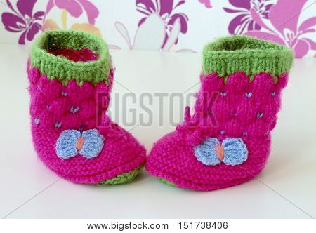 Baby booties shoes for newborn. Warm knitted pink baby shoes with blue bows.