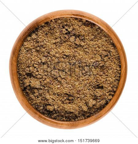 Muscovado dark brown sugar in a bowl over white. Also called Khaand, unrefined non-centrifugal cane sugar with strong molasses content and flavor from the Philippines, used in baking and making rum.