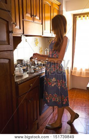 Breakfast - girl in the kitchen pouring coffee in a cup from the coffeepot