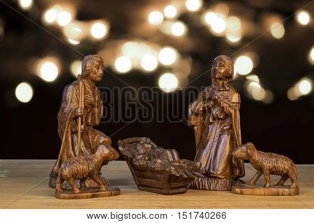 Christmas Scene With Figurines. Baby Jesus, Mary, Joseph On Light Bokeh Background.