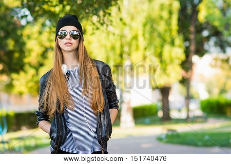 Cool teenage girl with headphones in sunglasses and urban outfit in park. Portrait of modern millennial young woman with long blonde hair, in black beanie and leather jacket. Natural light, vibrant colors.
