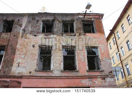 Abandoned destroyed damaged rundown old apartment house building facade with broken glass windows. Renovation, construction, building, architecture, exterior concept Close up  wall texture detail